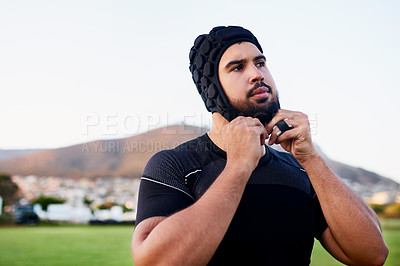 Buy stock photo Cropped shot of a handsome young sportsman wearing headgear and standing alone during rugby practice during the day