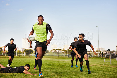 Buy stock photo Full length shot of a diverse group of sportsmen playing a game of rugby during the day