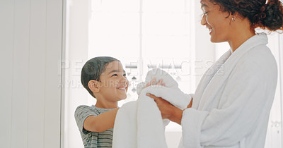 Buy stock photo Cropped shot of a mother helping her adorable young son wipe his hands with a bathroom towel at home