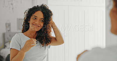 Buy stock photo Cropped shot of an attractive young woman styling her hair in her bathroom at home