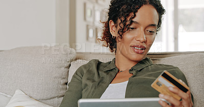 Buy stock photo Cropped shot of an attractive young woman using her credit card and digital tablet at home