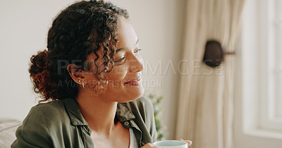 Buy stock photo Cropped shot of an attractive young woman drinking coffee and looking out the window inside her house