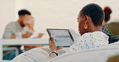 Buy stock photo Shot of a young businesswoman using a digital tablet while relaxing on a beanbag in a modern office