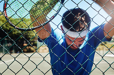 Buy stock photo Cropped shot of a handsome young sportsman taking a moment to breathe during tennis practise