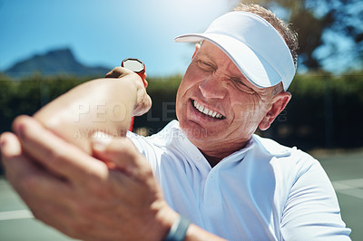 Buy stock photo Cropped shot of a handsome mature sportsman suffering from an elbow injury while playing tennis alone