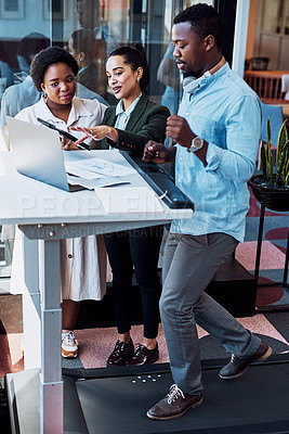 Buy stock photo Shot of a businessman walking on treadmill while having a meeting with his colleagues in an office