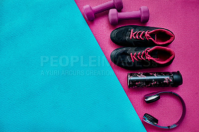 Buy stock photo High angle shot of a group of workout essentials lying on top of a colourful background  inside of a studio
