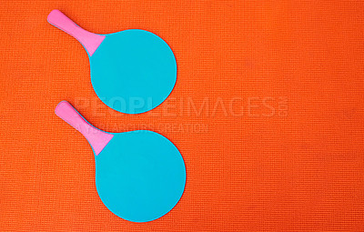 Buy stock photo High angle shot of two table tennis bats placed together on top of an orange background inside of a studio
