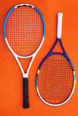 Buy stock photo High angle shot of two tennis rackets placed on an orange background inside of a studio