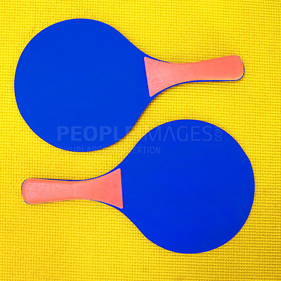 Buy stock photo High angle shot of two blue table tennis rackets placed on top of a yellow background inside of a studio