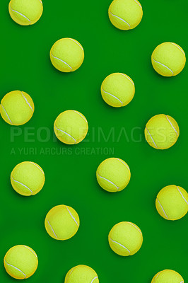 Buy stock photo High angle shot of a group of tennis balls placed together in formation on top of a green background inside of a studio