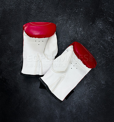 Buy stock photo High angle shot of a pair of boxing gloves placed together on top of a dark background inside of a studio