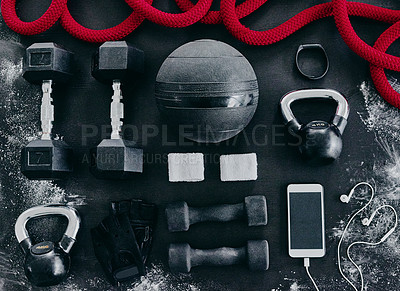 Buy stock photo High angle shot of fitness workout essentials placed on top of a dark background inside of a studio