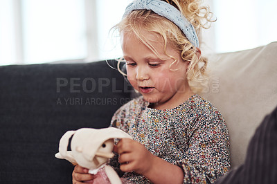 Buy stock photo Cropped shot of an adorable little girl sitting alone on the sofa and playing with her toys at home