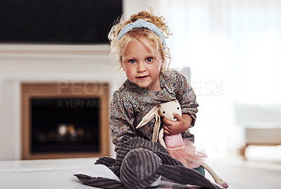 Buy stock photo Cropped portrait of an adorable little girl standing alone in the living room and playing with her toys at home