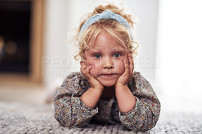 Buy stock photo Cropped portrait of an adorable little girl lying alone on the living room floor at home