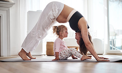 Buy stock photo Full length shot of an adorable little girl feeling playful while her mother does yoga in the living room