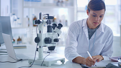 Buy stock photo Shot of a scientist writing notes while using a microscope in a lab