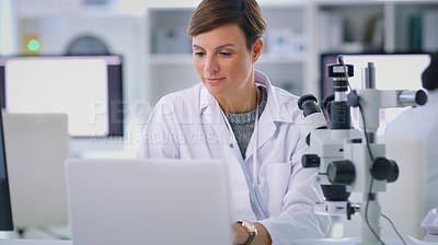 Buy stock photo Shot of a scientist using a laptop in a lab
