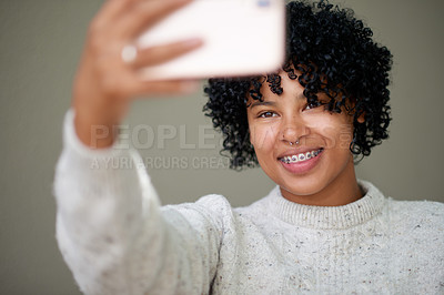 Buy stock photo Studio shot of a young woman taking selfies against a grey background