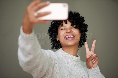 Buy stock photo Studio shot of a young woman making a peace sign with her fingers while taking selfies against a grey background