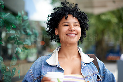 Buy stock photo Shot of a young woman drinking coffee while out in the city