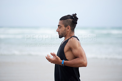 Buy stock photo Shot of a handsome young man exercising and practicing yoga outdoors at the beach
