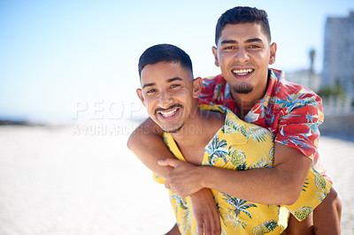 Buy stock photo Cropped portrait of a handsome young man giving his boyfriend a piggyback ride during a day on the beach