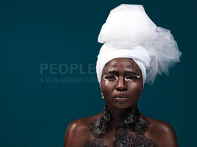 Buy stock photo Studio portrait of an attractive young woman posing in traditional African attire against a blue background