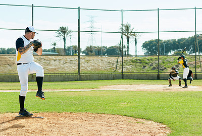 Buy stock photo Full length shot of a handsome young baseball player pitching a ball during a match on the field