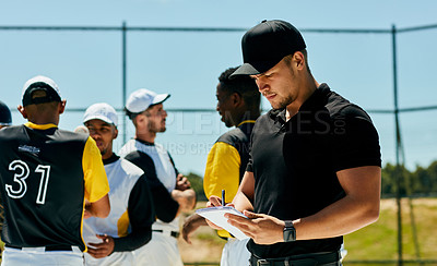 Buy stock photo Cropped shot of a handsome young baseball coach writing on a note pad while standing on the field during the day
