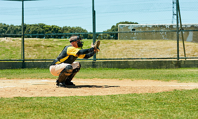 Buy stock photo Full length shot of a young baseball player preparing to catch a ball during a match on the field