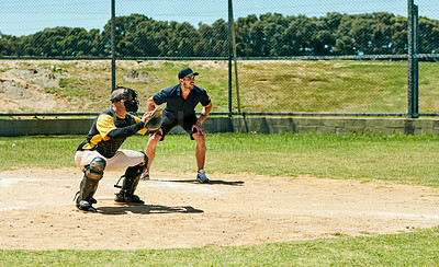 Buy stock photo Full length shot of a young baseball catcher waiting to catch a ball at home base during a match on the field