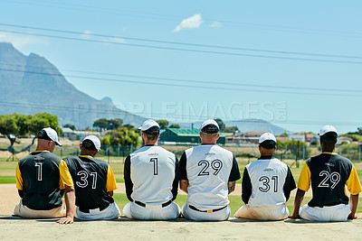 Buy stock photo Rearview shot of a team of unrecognizable baseball players sitting together near a baseball field during the day