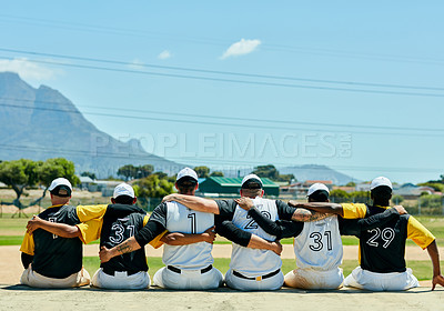 Buy stock photo Rearview shot of a team of unrecognizable baseball players embracing each other while sitting near a baseball field during the day