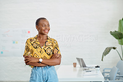 Buy stock photo Shot of a young businesswoman looking thoughtful while standing with her arms crossed in an office