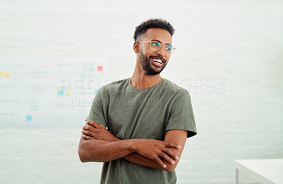 Buy stock photo Shot of a young businessman looking thoughtful while standing with his arms crossed in an office