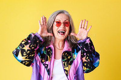 Buy stock photo Cropped shot of a confident and stylish senior woman wearing sunglasses posing against a yellow background