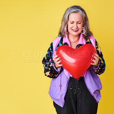 Buy stock photo Cropped shot of a confident and stylish senior woman holding a heart shaped balloon against a yellow background