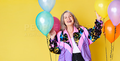 Buy stock photo Portrait of a cheerful and stylish senior woman posing with balloons against a yellow background