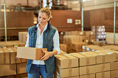 Buy stock photo Cropped shot of an attractive mature supervisor standing alone and holding a box in a warehouse