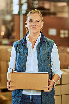 Buy stock photo Cropped portrait of an attractive mature supervisor standing alone and holding a box during a stocktake in a warehouse