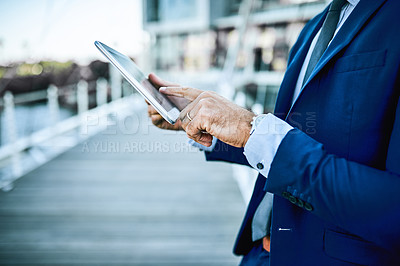 Buy stock photo Cropped shot of an unrecognizable businessman using a digital tablet while standing outside