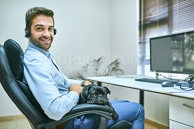 Buy stock photo Shot of a call centre agent wearing his headset while sitting with his dog in the office