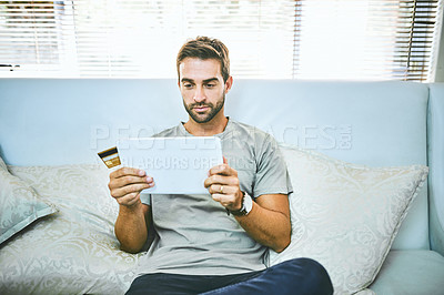 Buy stock photo Shot of a man holding his credit card while using a digital tablet