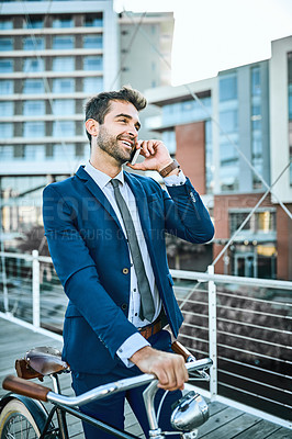Buy stock photo Shot of businessman talking on his cellphone while walking through the city with his bicycle