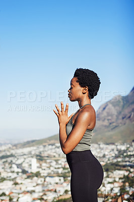 Buy stock photo Cropped shot of an attractive young woman meditating while standing outdoors during the day