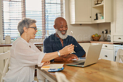 Buy stock photo Cropped shot of a happy mature couple using a laptop while going over their bills and finances together at home