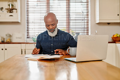 Buy stock photo Cropped shot of a mature man going over his finances and paperwork at home