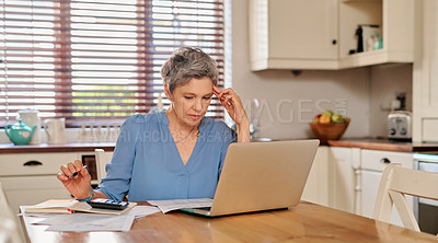 Buy stock photo Cropped shot of a mature woman looking concerned while using a laptop and going over her finances at home